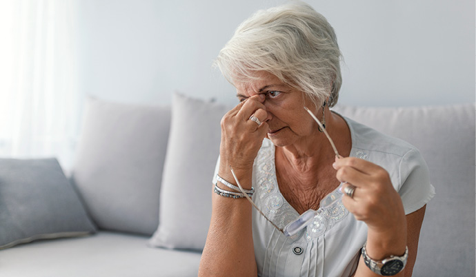 woman holding her nose in pain