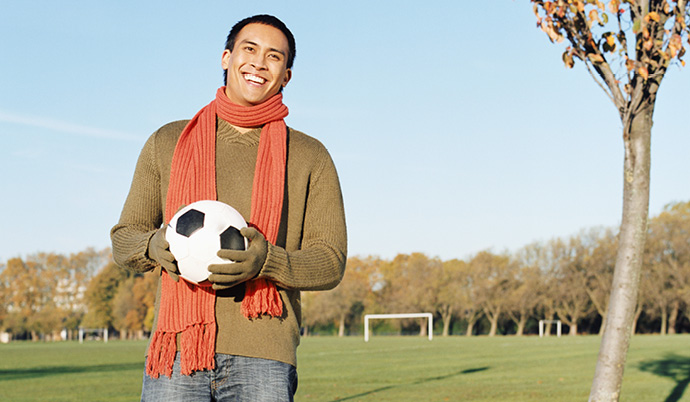 guy holding a soccer ball outside
