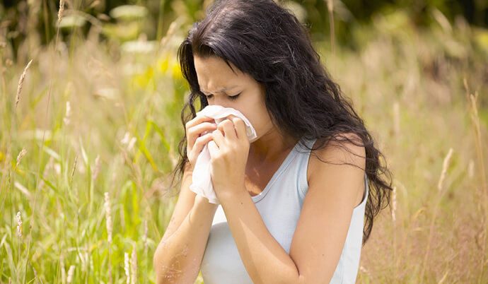 woman sneezing outside in a field