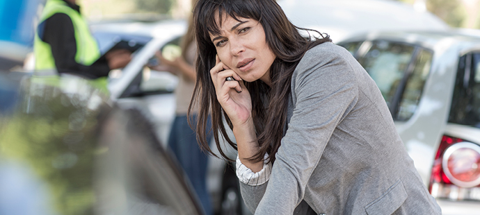 woman talking on the phone at a car accident