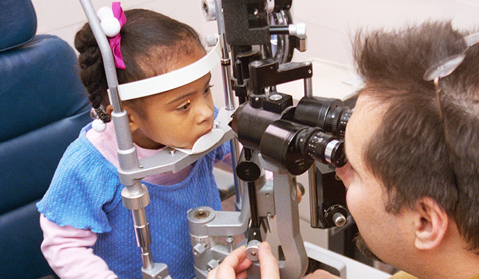 doctor examining a young girls eyes