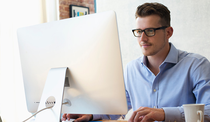 man with glasses working at a computer