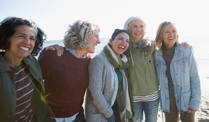 five woman smiling together outside