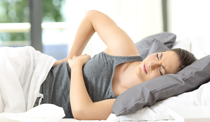 woman laying down with side pain