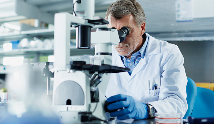 doctor looking at a slide through a microscope
