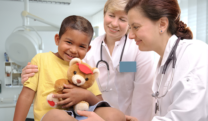 doctor giving a young boy a teddy bear