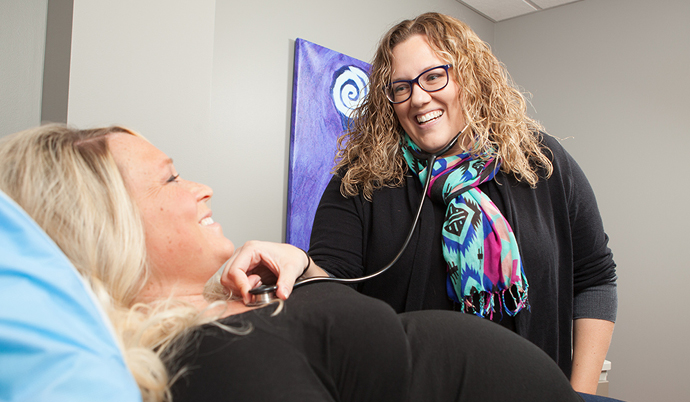 doctor listening to heart beat of pregnant woman