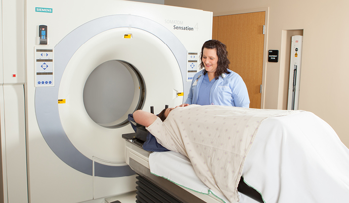 A provider helping a patient with a CT scan.