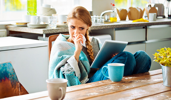 woman sick at home using an ipad