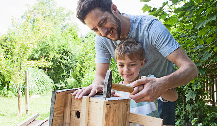 dad and son building a birdhouse