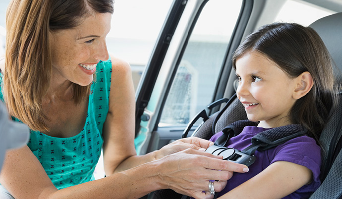 mom fastening child in a car seat